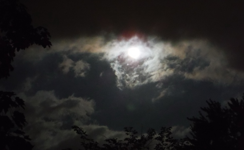 Moon behind clouds at night.