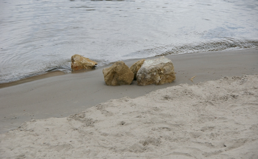 Sandy beach with a cluster of large limestone rocks.