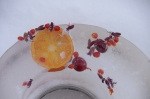 Ice ring luminary (outdoor candle holder) with orange, cranberries, and berries from a burning bush.