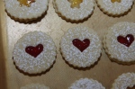 Linzer sandwich cookies with heart cut-outs and red jam.
