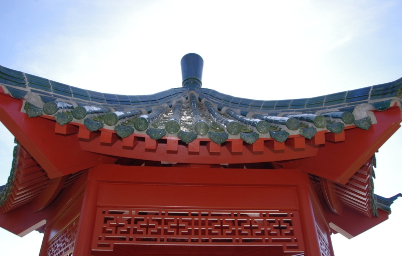Sun washed-out sky over the green tiled roof of a Chinese pavilion.