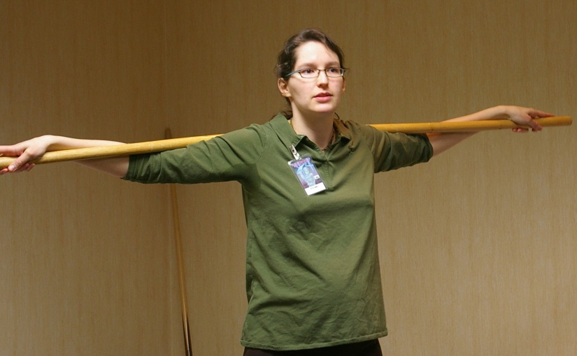 Woman with a bo staff across her shoulders.