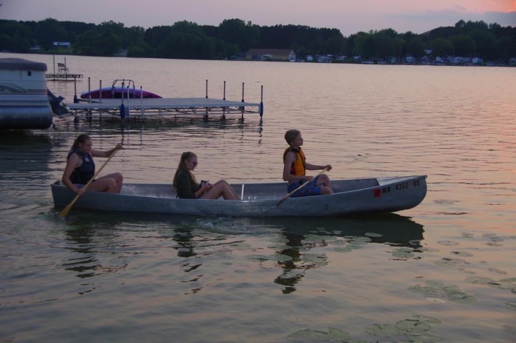 Kids in a canoe near sunset.
