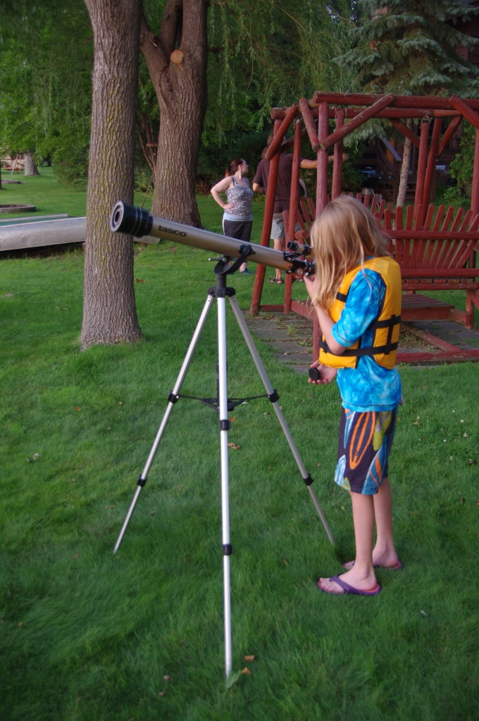 Child in a swimsuit and lifejacket looking through a telescope.