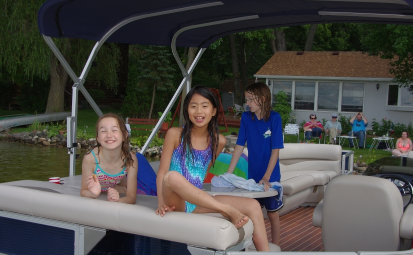 Kids sitting on the back of the pontoon.