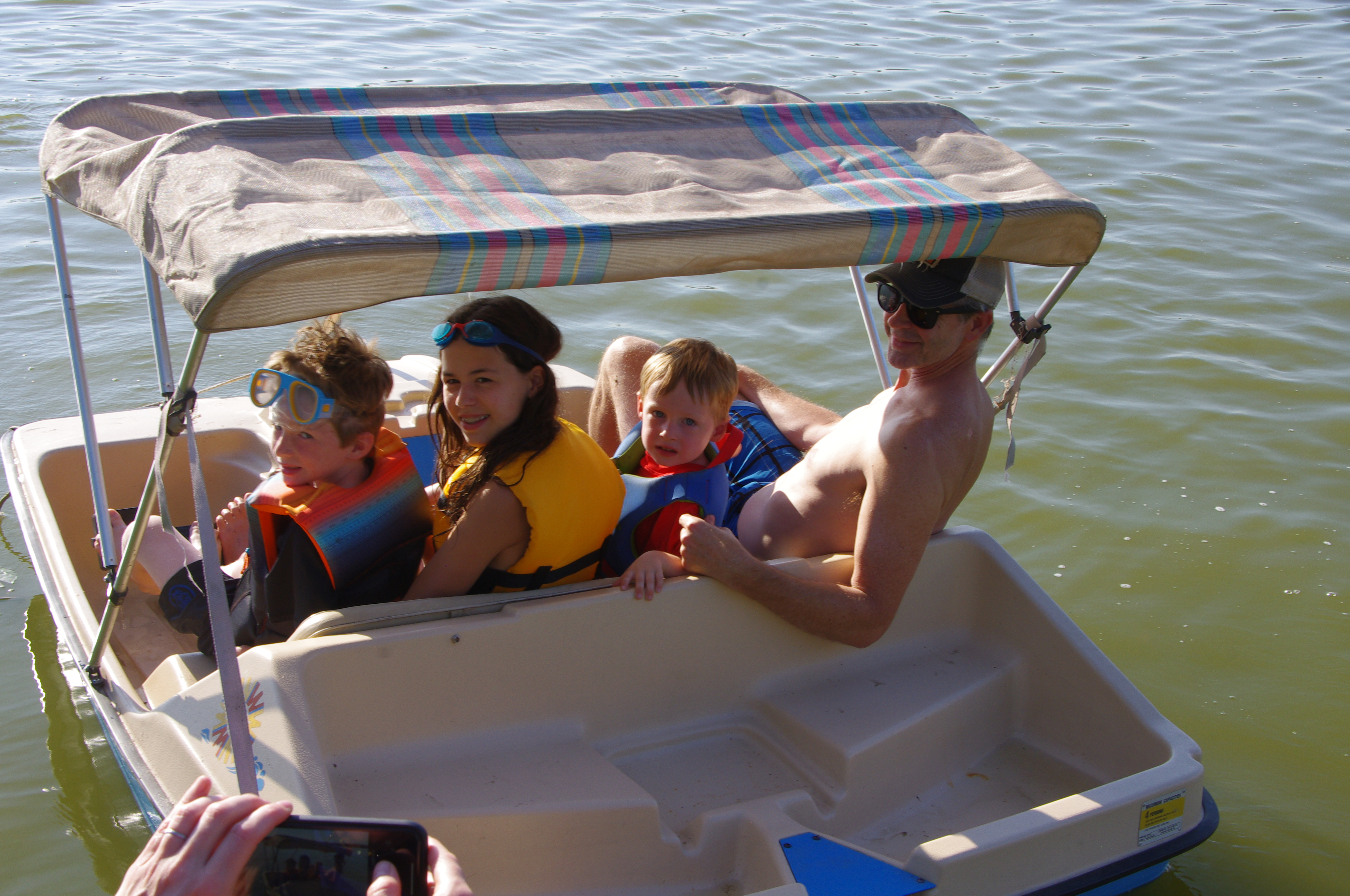 Three kids and an adult in a peddle boat.