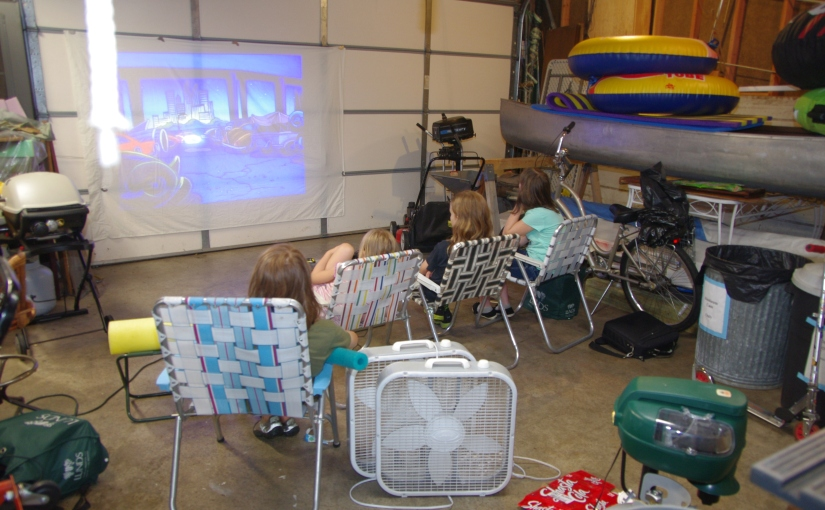 Kids in lawn chairs watching a movie projected on the door of a garage.