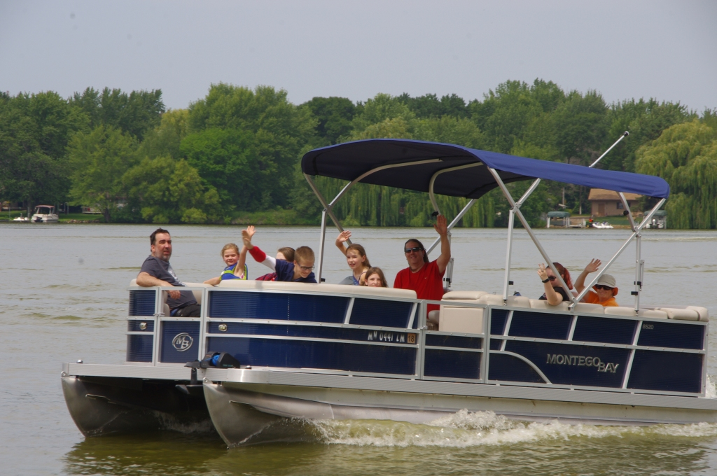 Group of people on a pontoon boat waving.